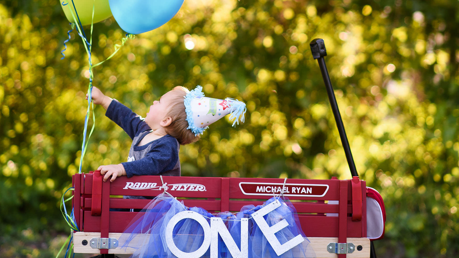 One year old in a wagon reaching for a balloon during a family photography session in Greenville,SC.