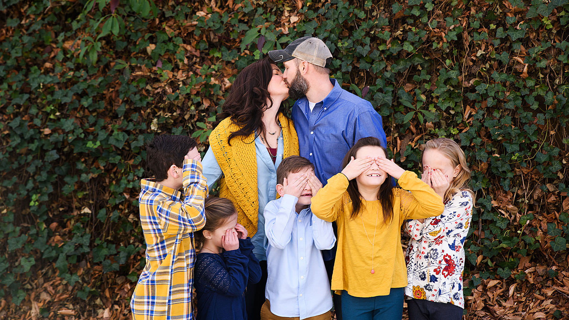 Creative shot of a family where the mom and dad are kissing while the children are holding their eyes shut.