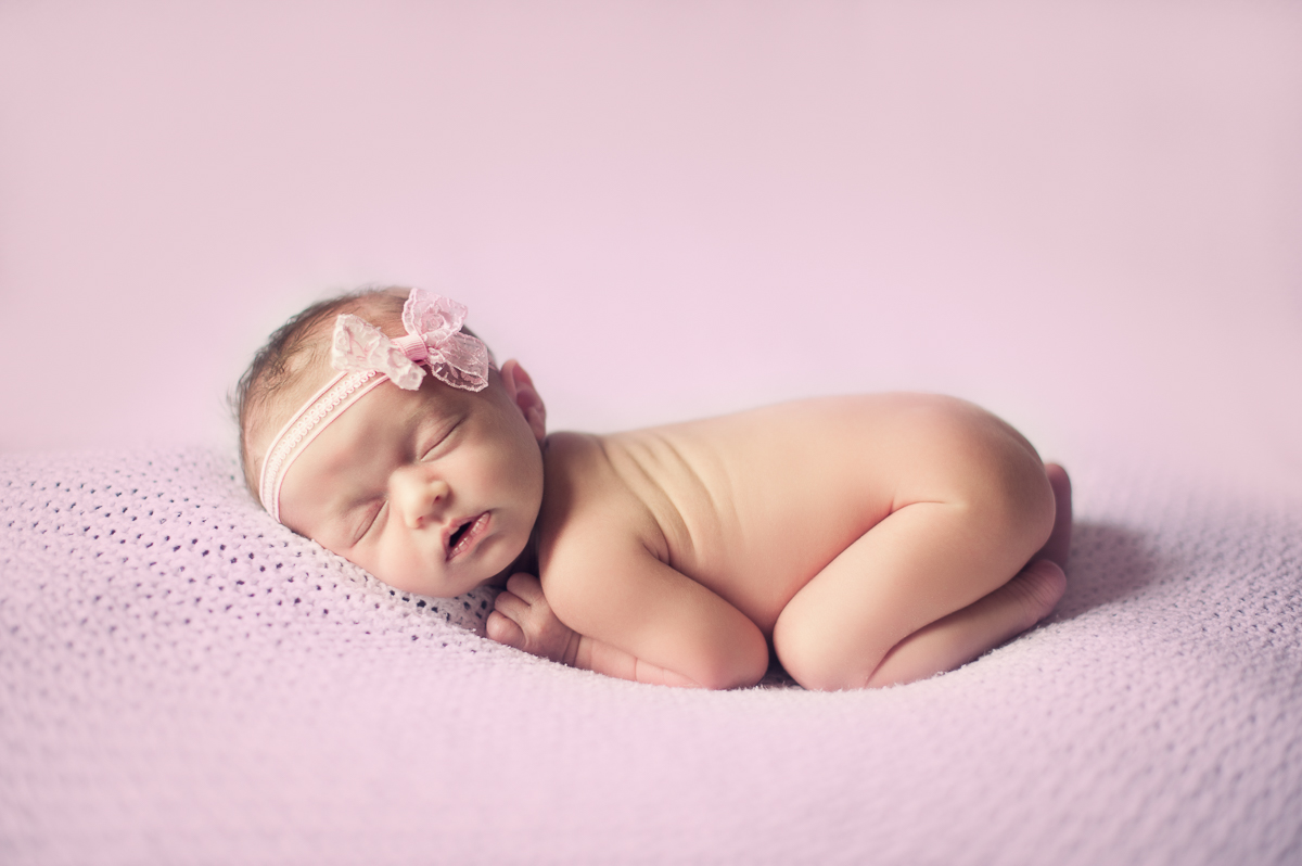 Newborn baby girl sleeping during a photo session.