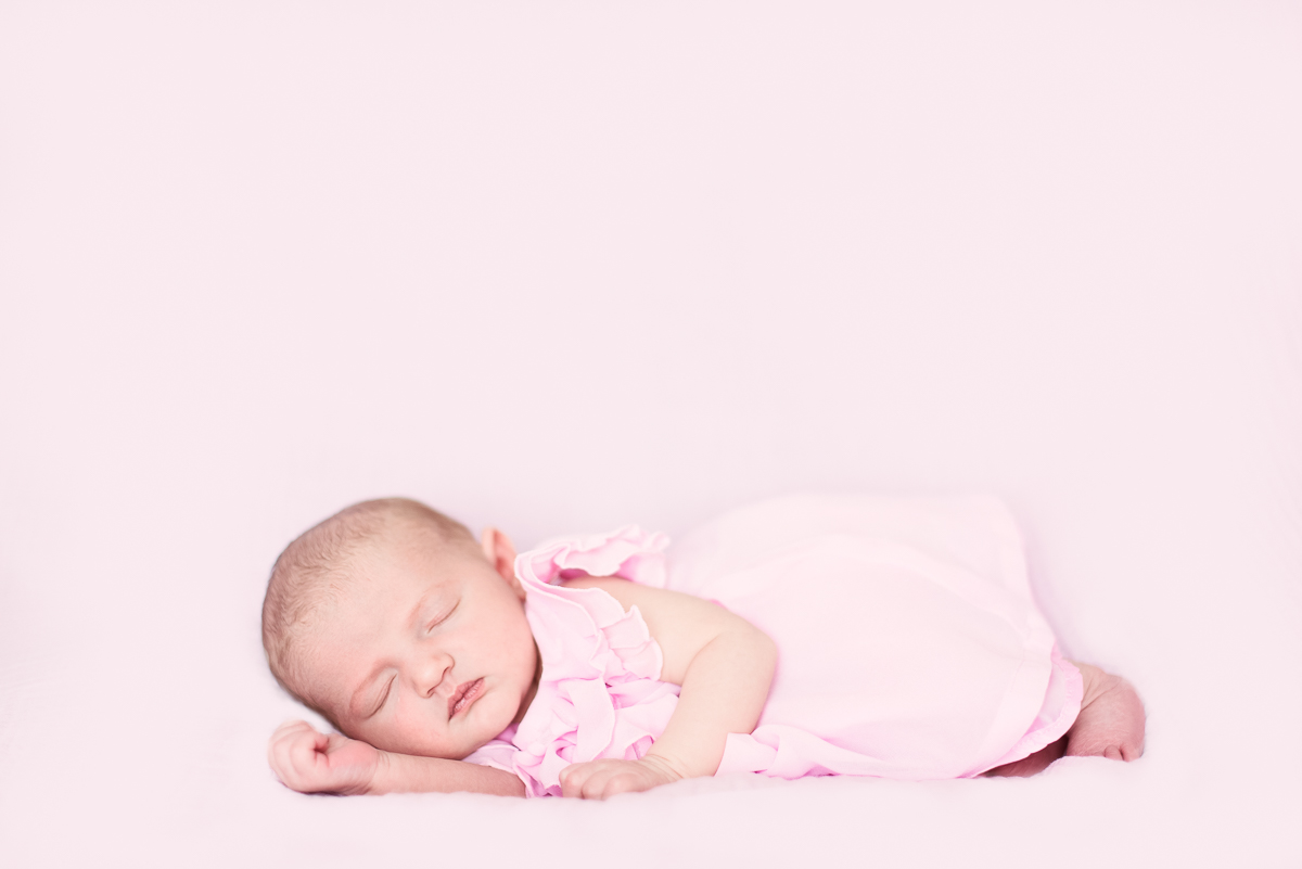 Baby girl in a pink dress laying on her side.