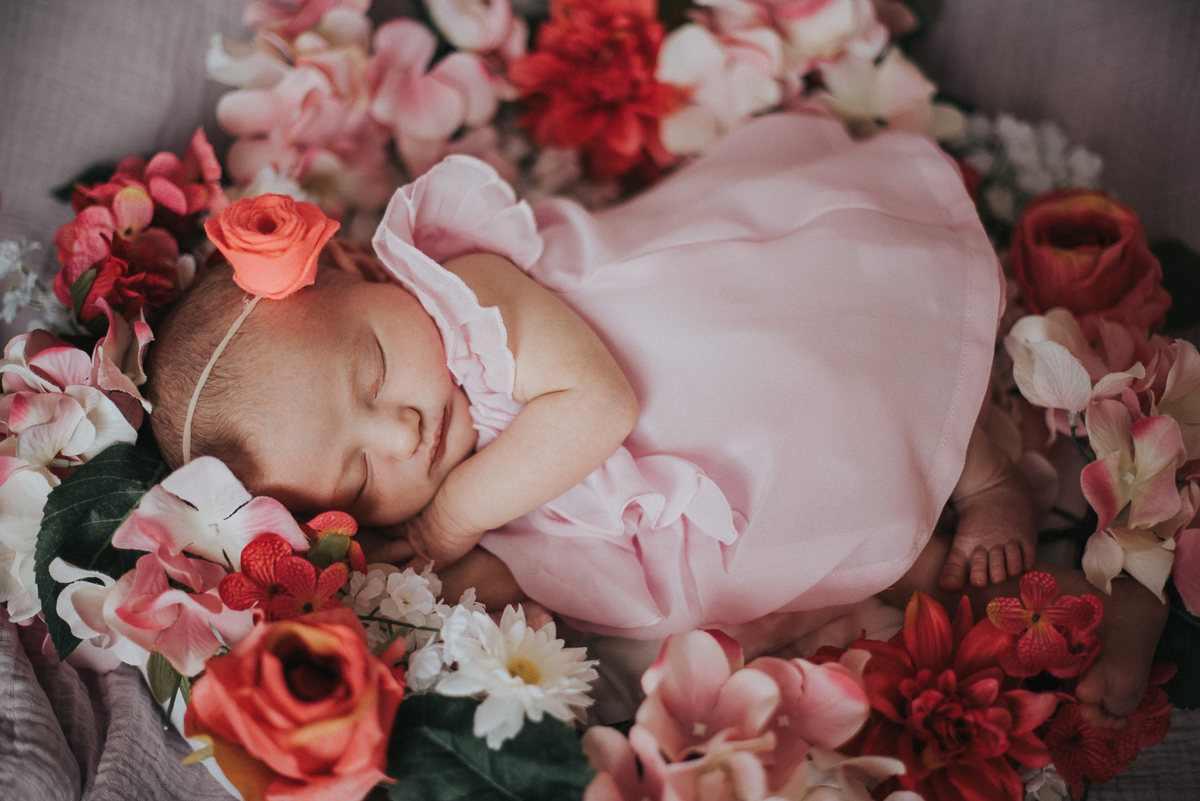7 day old baby girl laying in flowers wearing a pink dress by Greenville SC Newborn Photographer Elizabeth and Charles.