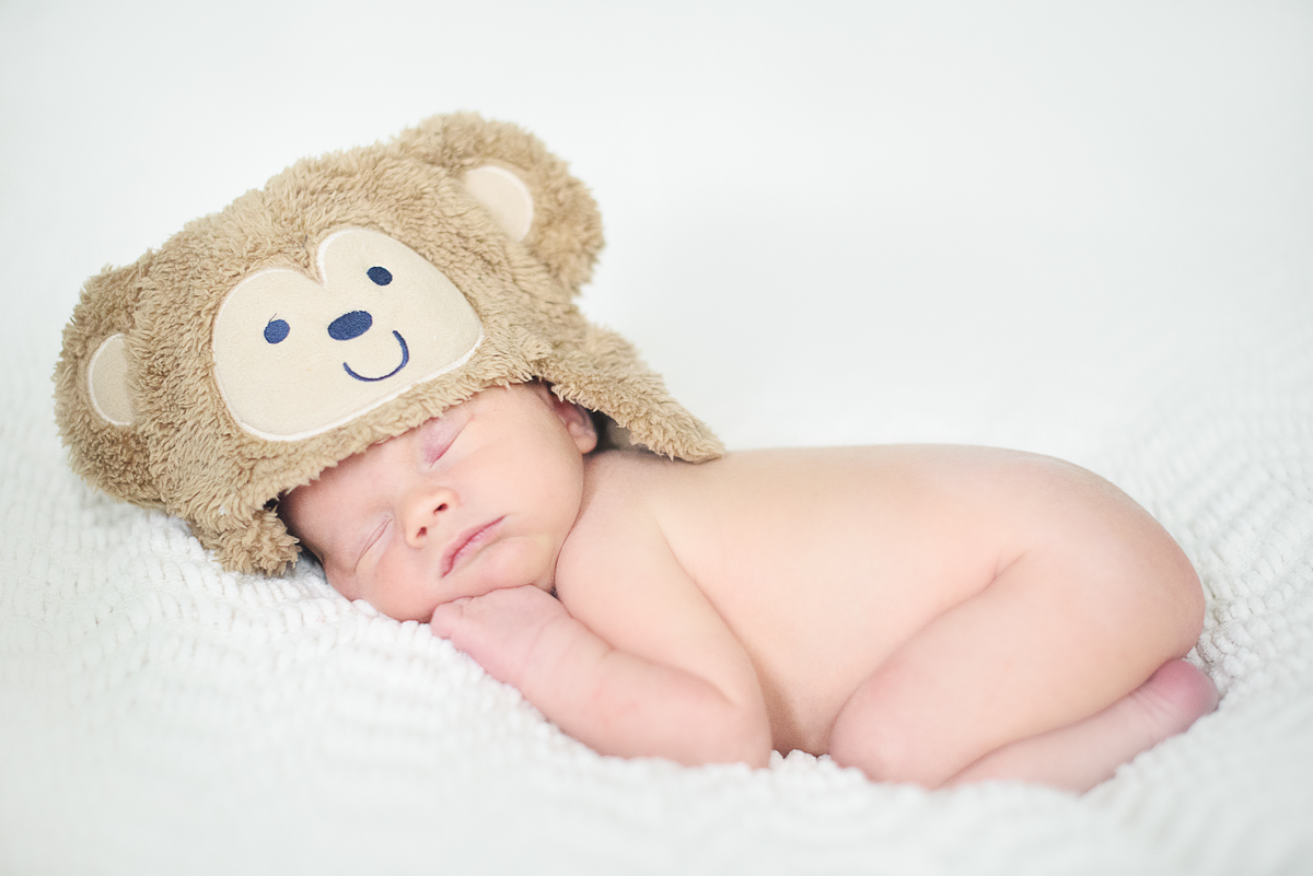 Newborn baby boy wearing a teddy bear hat.